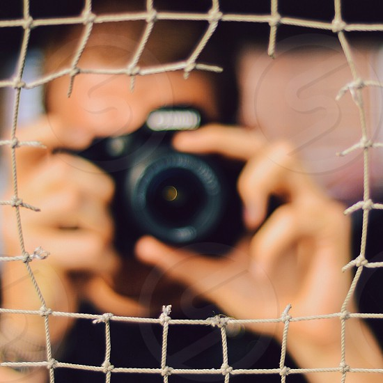 man taking a photo through a hole in a wire fence photo