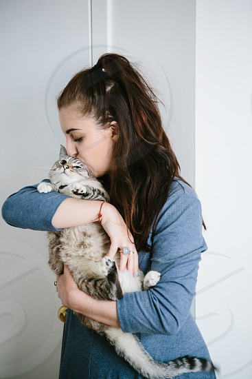 woman kissing silver tabby cat photo