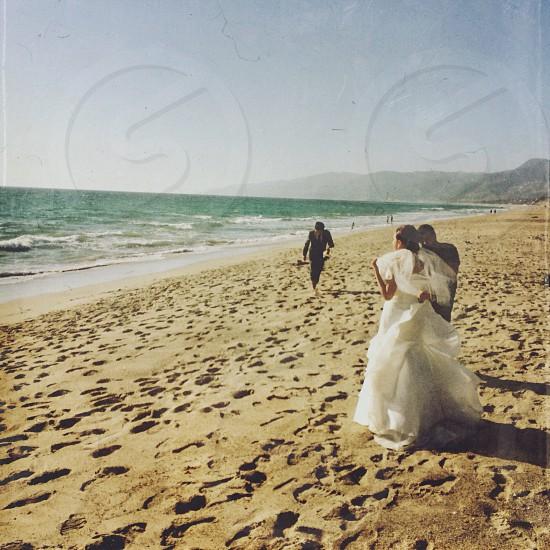 man in black formal suit walking toward woman in white bridal gown in seashore during daytime photo
