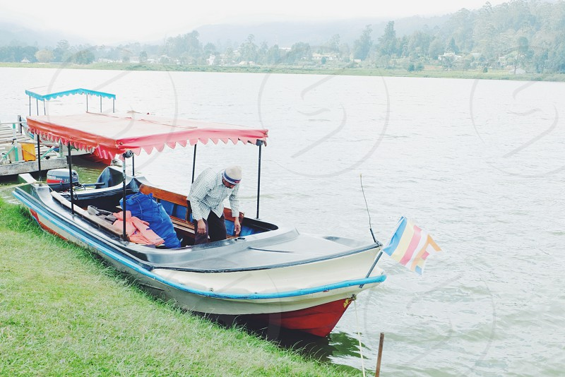man on white motor boat photo