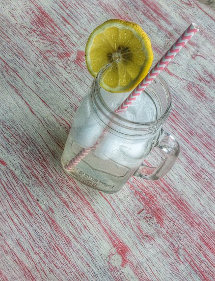 mason jar with clear beverage and lemon slice with white and pink striped straw photo