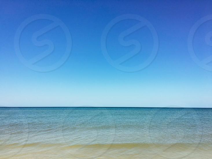 Ocean sea calm peace serene blue symmetry nature coast beach sky beautiful photo