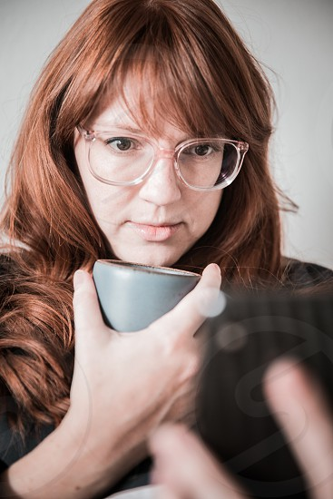 A woman holding a mug of coffee looking at her phone.  photo