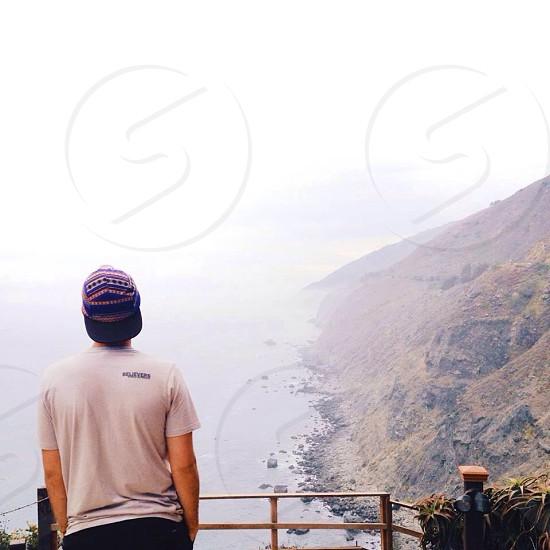 man in beige t-shirt facing lake photo