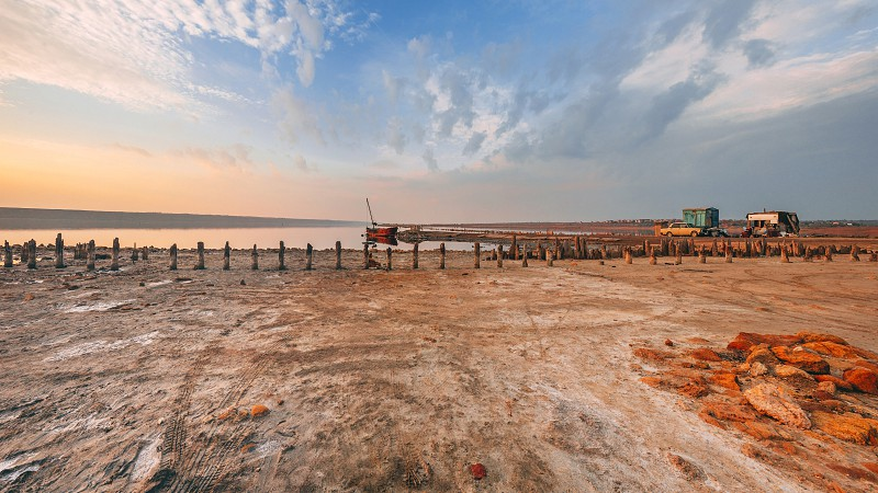 Shore and bottom of a drying lake at sunset photo