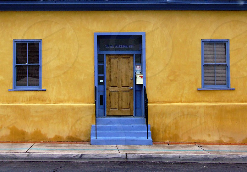 Bright blue framed door and two windows are on a vibrant orange adobe building photo