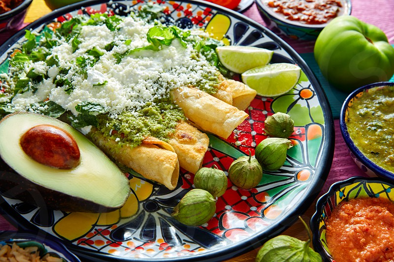 Green enchiladas Mexican food with guacamole and sauces on colorful table photo