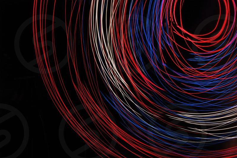A set of red white and blue lights spinning in circles. Light painting with red white and blue. photo