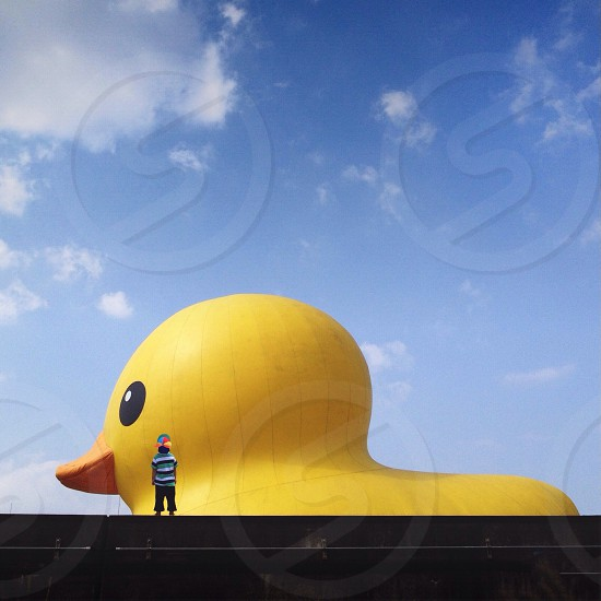 yellow and orange duck design structure with person standing in front photo