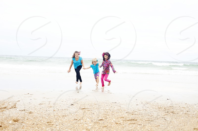 woman in blue holding the hands of 2 girls white standing on the beach photo