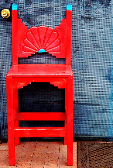 Bright red southwestern style chair stands i front of a blue door. photo