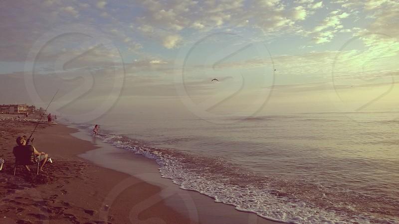 beachfishermanwatershorelineshoresandfishingrelaxingrelaxcalmmuted photo