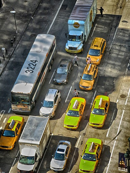 yellow cabs a bus and cars driving on street photo