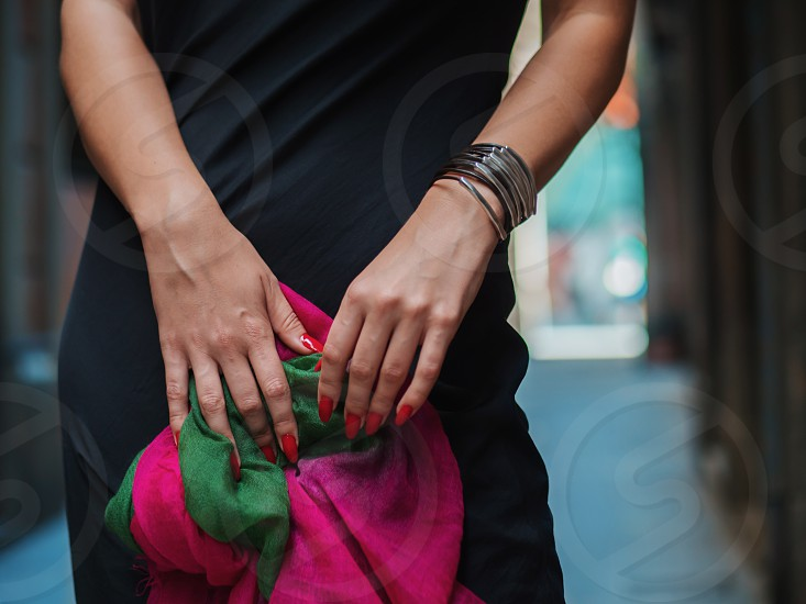 Female hands of unrecognizable beautiful young woman holding colorful shawl in the empty street. photo