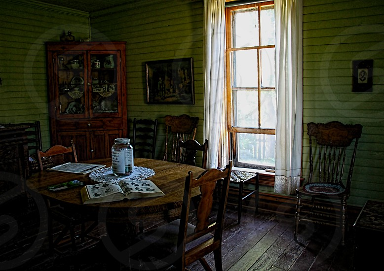 Morning light streams through a window into a farmhouse dining room at breakfast time. photo