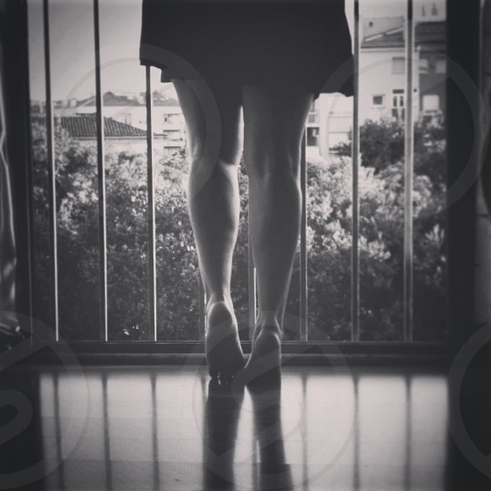 woman wearing a black skirt leaning over a balcony railing photo