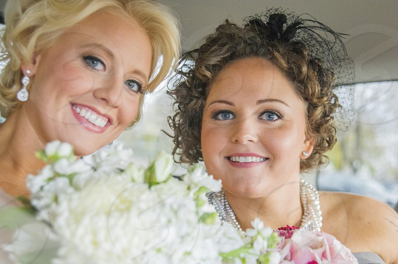 two women with white flowers and pearl necklace photo