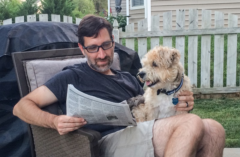 Owner and dog relaxing and bonding on the back patio. photo