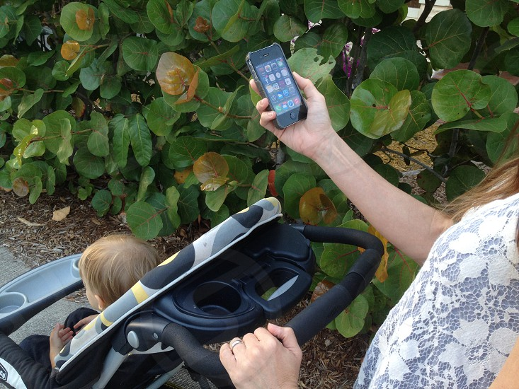 person holding a black i phone and a black and blue baby stroller  photo