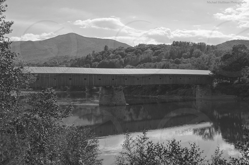 black and white covered bridge over river photo