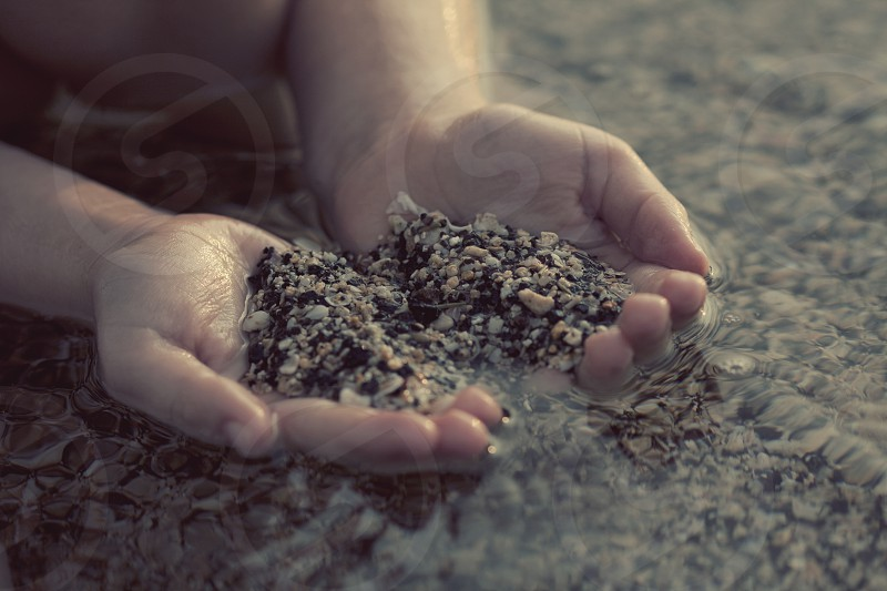 person carrying white and black sea pebbles photo