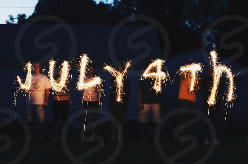 Fire sparklers night Fourth of July July 4th friends camping dark sky fireworks celebrate photo