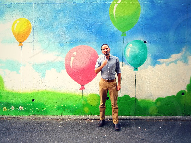 man in blue shirt in front of mural of colorful balloons photo