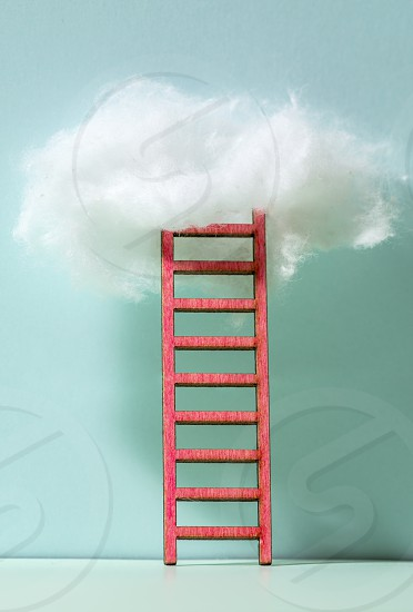 Red ladder to the clouds metaphor. Concept for growth and internet cloud networking. Blue wall. photo