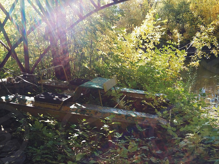 Old pedalo vehicle parked on ground near little river photo