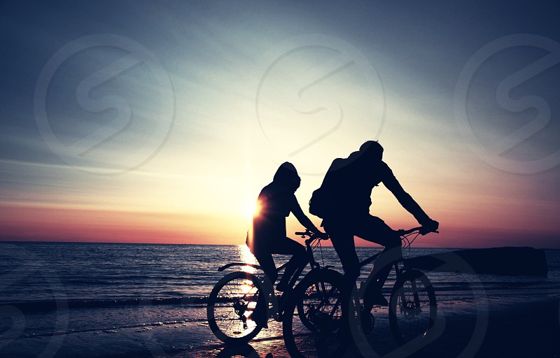 two persons riding bicycle beside seashore under blue and orange sky photo
