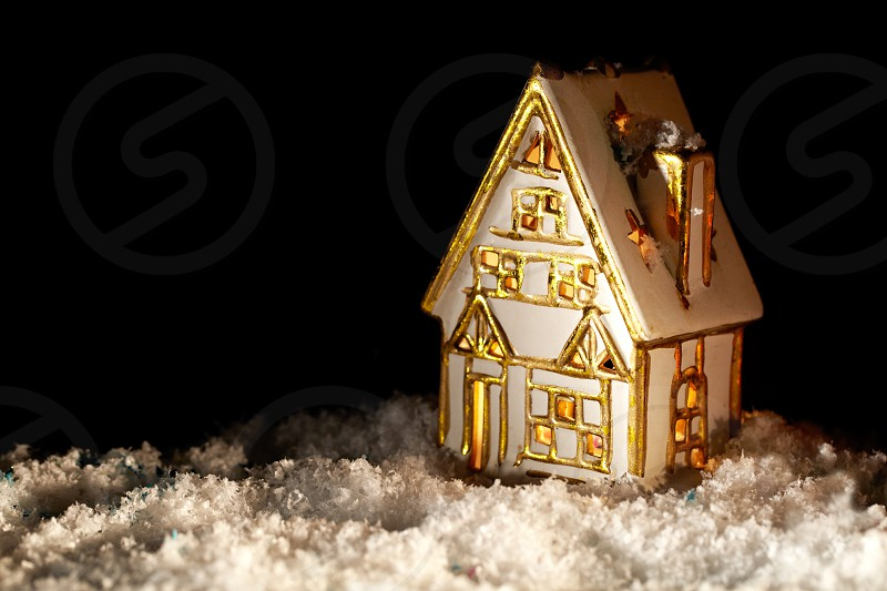 Little cozy toy house covered with artificial snow. Nice and warm background with copyspace for your greetings. photo