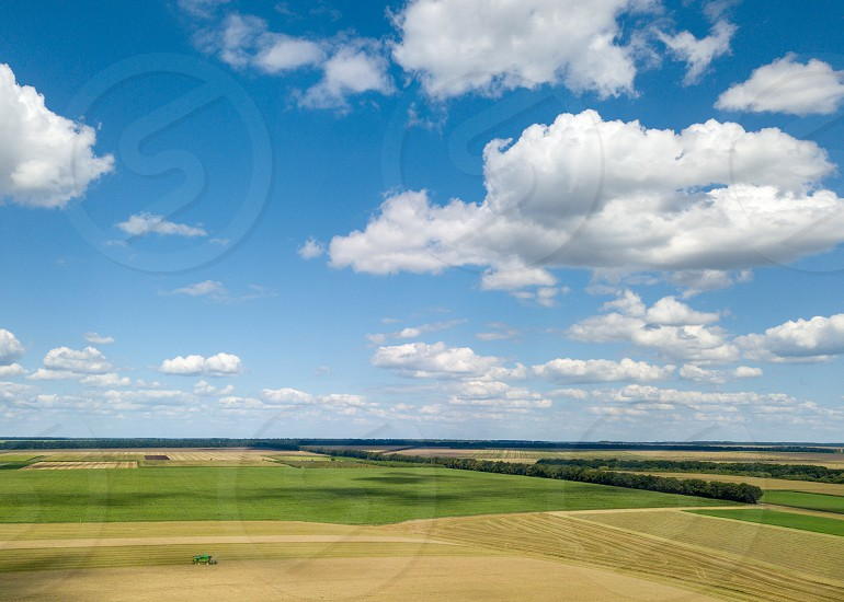 Aerial panoramic view from drone of agricultural fields with harvesting of a combine and blue sunny sky white clouds in a summer day at sunset. photo