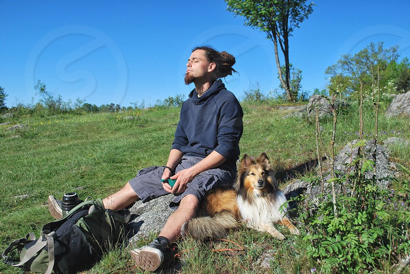 man with collie dog on rock in park eyes closed with backpack photo