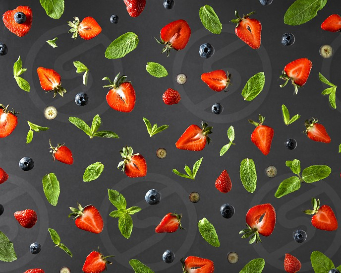 Top view of colorful composition of strawberry red ripe blueberry and green sprig of mint isolated on black background photo