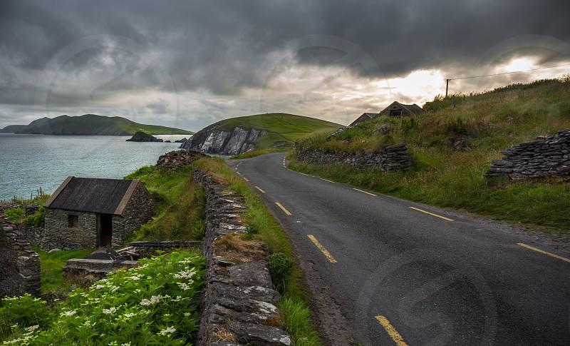 gray concrete road near sea photo