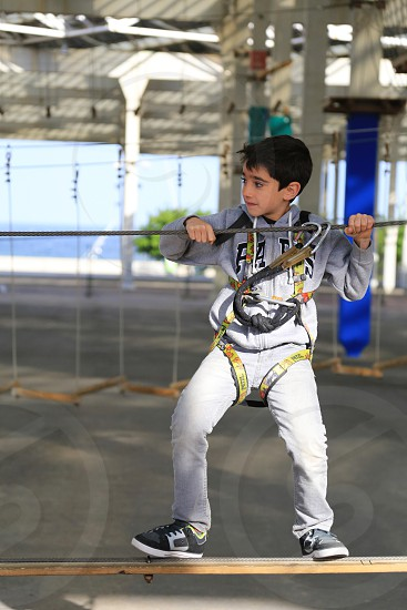 little boy make climbing in the tie park. Concept of sport life. photo
