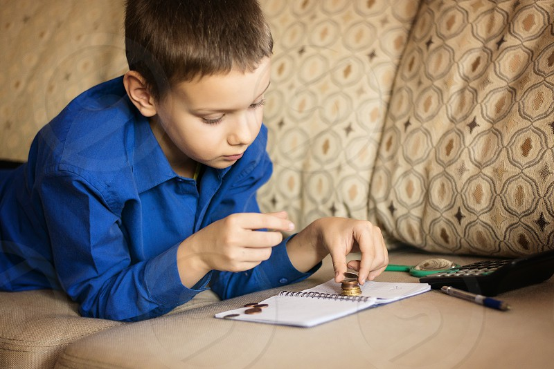 boy child childhood education finance cash coins dollar concentration looking learning school indoor couch calculator photo