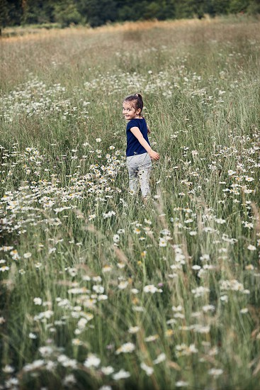 Little happy girl playing in a tall grass in the countryside. Candid people real moments authentic situations photo
