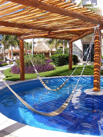 2 hammock on hanged on a brown wooden post on top of a swimming pool photo