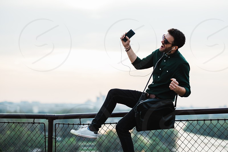 Young man listening to the music on his smartphone photo