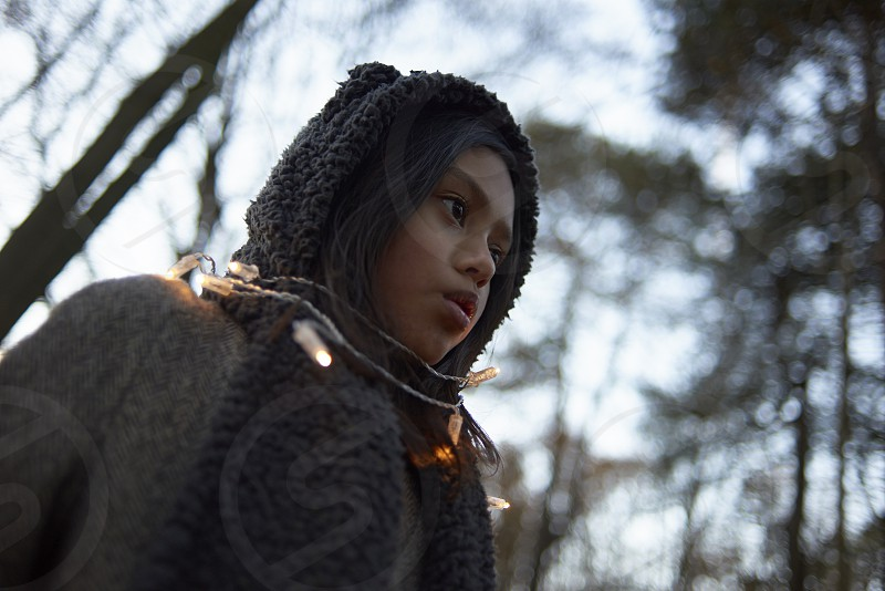 Portrait of a young Asian girl in a forest during autumn at dusk wearing a string of lights around her in a magical setting photo