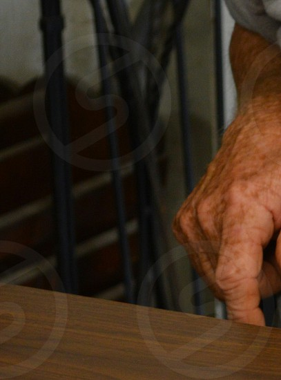 right human arm near a brown wooden table photo