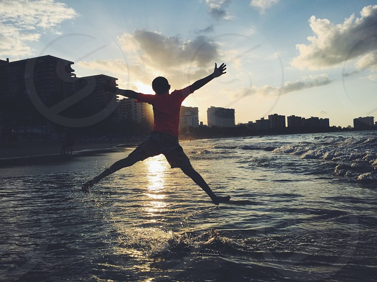 Fun family beachCaribbean boy sunset jumping ocean vacations  photo