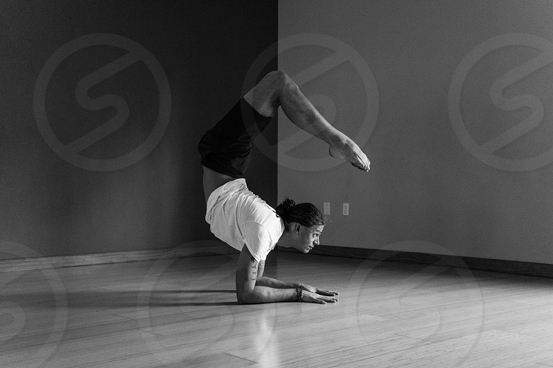 woman with hair tied back in white t shirt and black shorts on forearms with legs over head in yoga pose on wood floor in corner of room greyscale photo photo