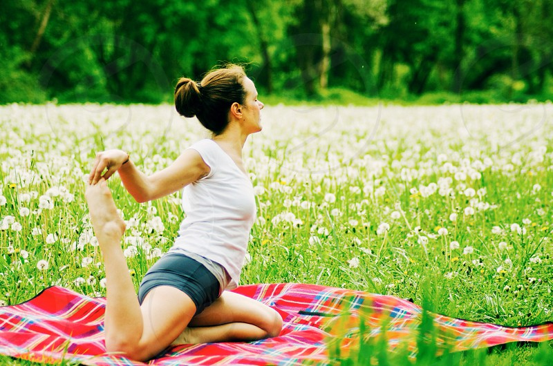brunette woman in white t shirt and black rolled shorts on red plaid blanket stretching in yoga pose in green grass and white dandelions photo