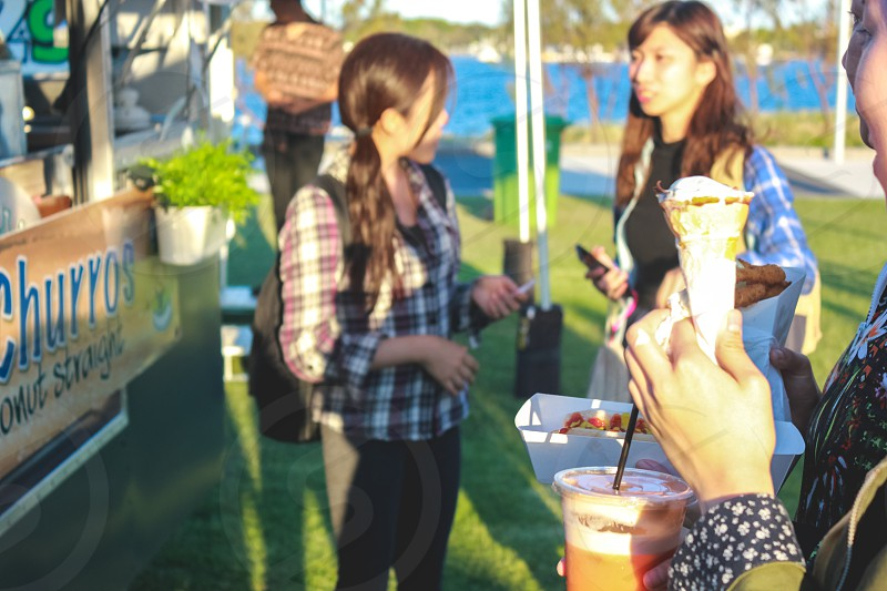 young people enjoying refreshments from the food trucks on a sunny spring day at the music festival  photo