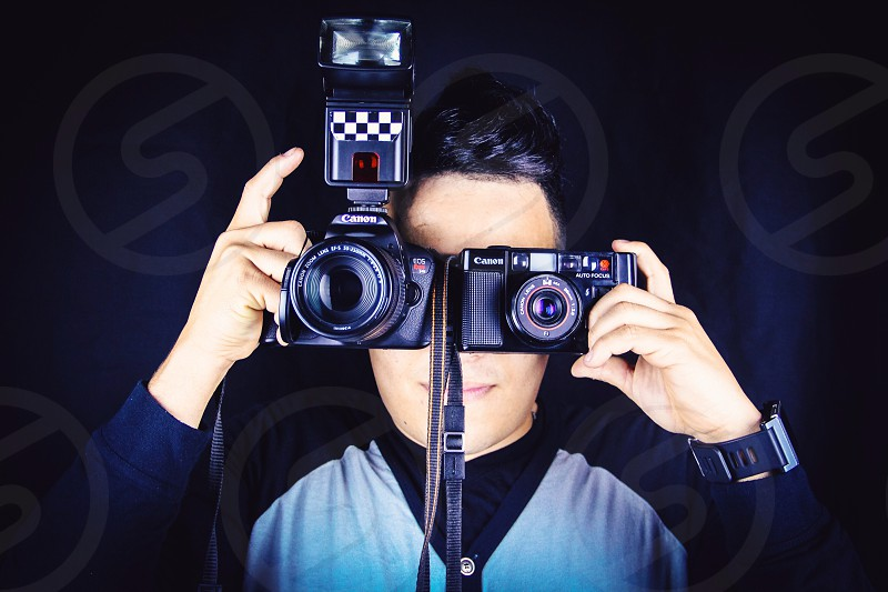 person taking pictures with two cameras photo