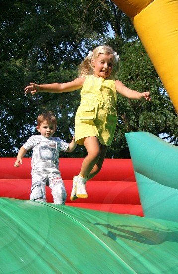 girl in yellow sleeveless jumper jumping on water slide in front of boy in white photo