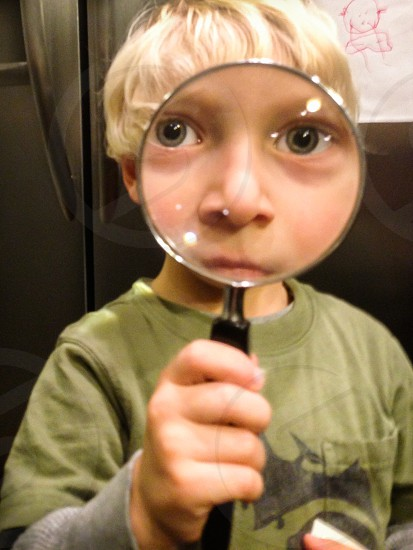 boy youth child magnify magnifying glass play playing silly looking eyes wide eyes big eyes glass green dinosaur blonde hair hand handle nose close-up face refrigerator photo