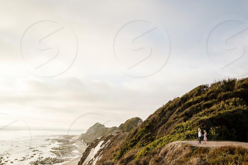 people on rocks next to ocean photo